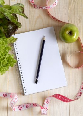 Empty notebook with vegetable salad and apple