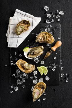 Fresh oysters on a black stone plate top view