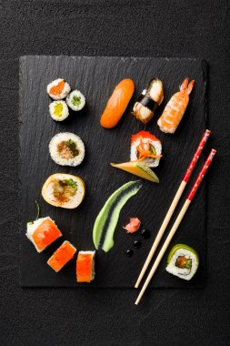 Sushi on black stone plate on a stone table top view