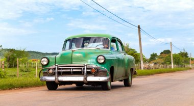 SANTA CLARA,CUBA - JUNE 23, 2014: Cuba green american vintage car driving on the road