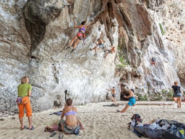 Rock climbers climbing the wall on Railay beach.