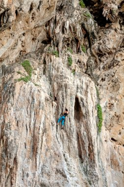 Incredible wall and young woman climbing, concept for overcoming