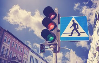Retro filtered photo of traffic lights and pedestrian crossing sign.