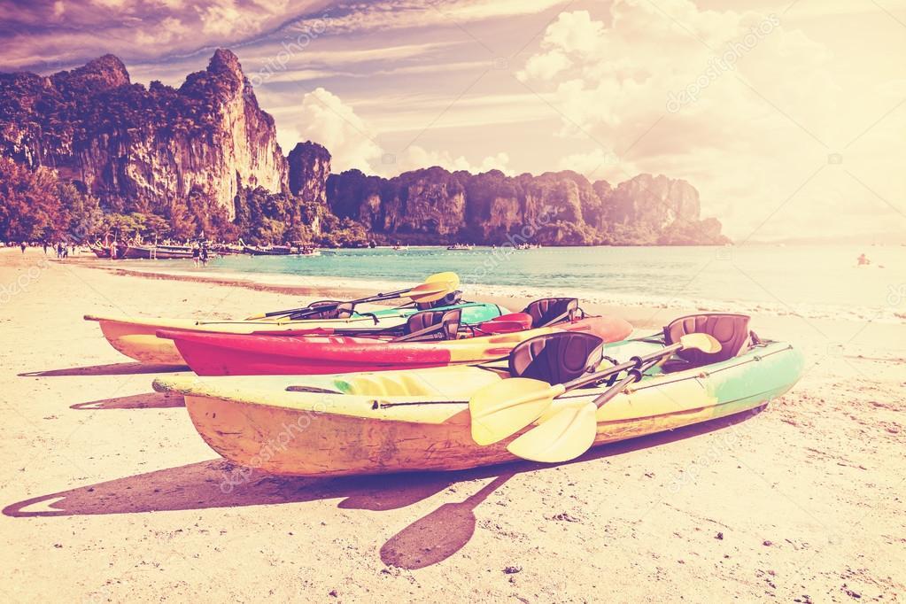 Retro toned kayaks on a tropical beach.