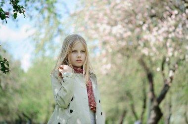 Girl walks in the lush apple orchard