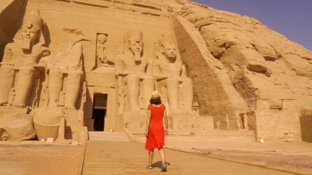 Mladá žena v červených šatech kráčí směrem k chrámu Abu Simbel v jižním Egyptě v Nubii vedle jezera Nasser. Temple of Pharaoh Ramses II, 4k video