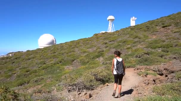 A young woman on the route of the telescopes on top of the Caldera de Taburiente volcano near Roque de los Muchachos one summer afternoon, La Palma, Canary Islands. Spain