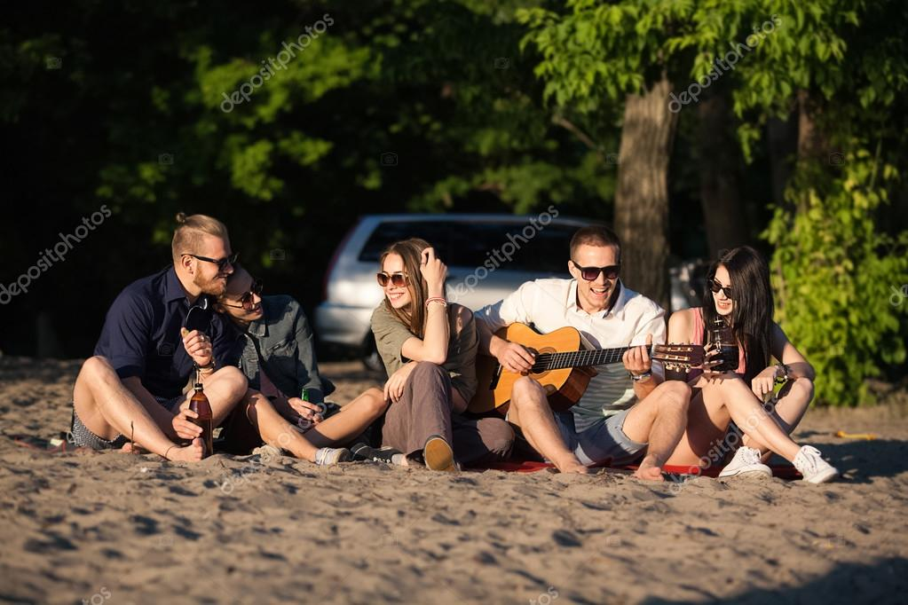 Group of  friends relaxing on sand at beach with guitar