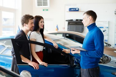 Car salesman giving key of  new car to  young  owners