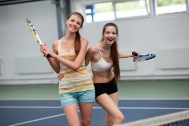 young women playing doubles  tennis at the court