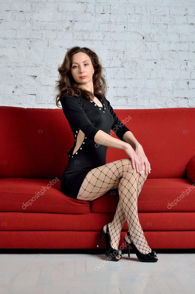 приличная девушка сидит на диване в короткой юбке может