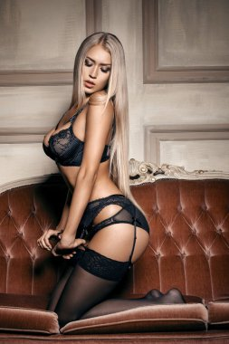 Sexy woman in seductive black lingerie sitting on a couch in stockings