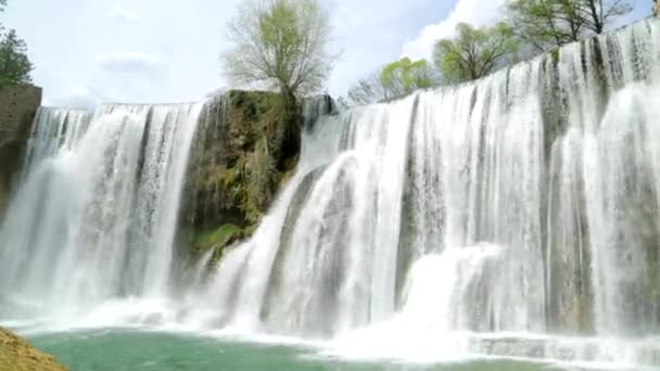 Vodopád v bosenském městě nedaleko lesa na zamračený den v městě Jajce, Bosna a Hercegovina