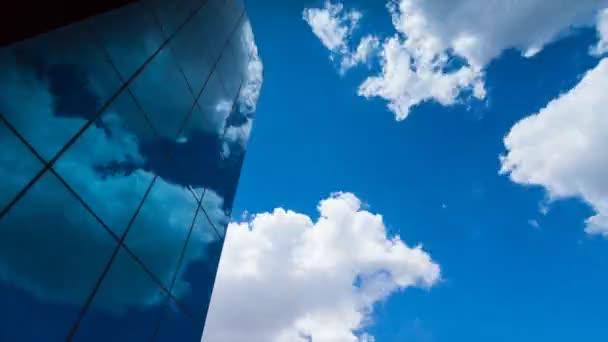 časová prodleva, díval se na prosklený mrakodrap, což odráží modré oblohy a pomíjivé mraky