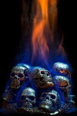 Burning skulls on black background