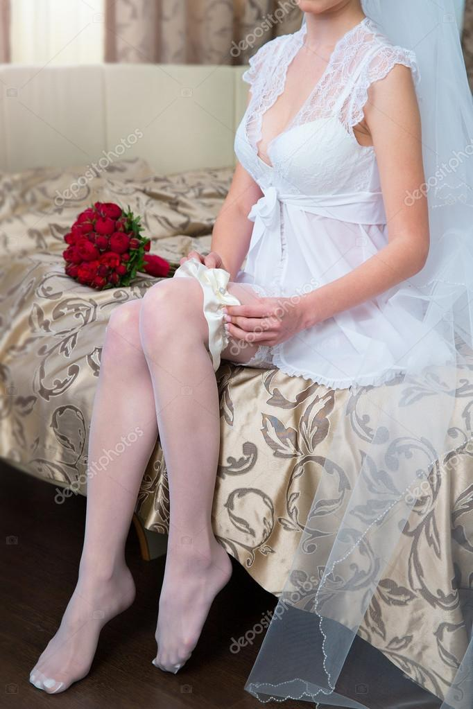 bride dresses garter on the leg. Picture of beautiful female bar