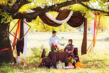 Beautiful Young Couple Having Picnic in autumn Park. Happy Famil