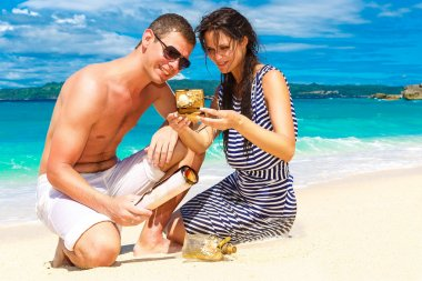 Happy young couple having fun on the shore of a tropical island.