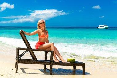 A beautiful young girl in bikini is sitting on a sun lounger coa