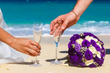 Wedding bouquet and two glasses of champagne on the sand. Male a