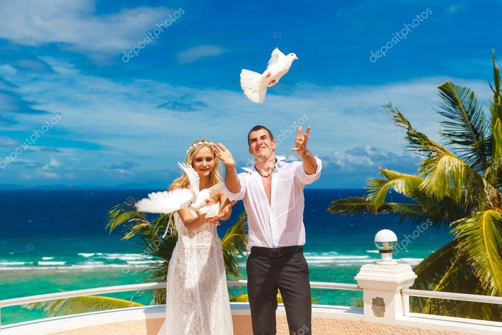 The happy bride and groom with white doves on a tropical beach u