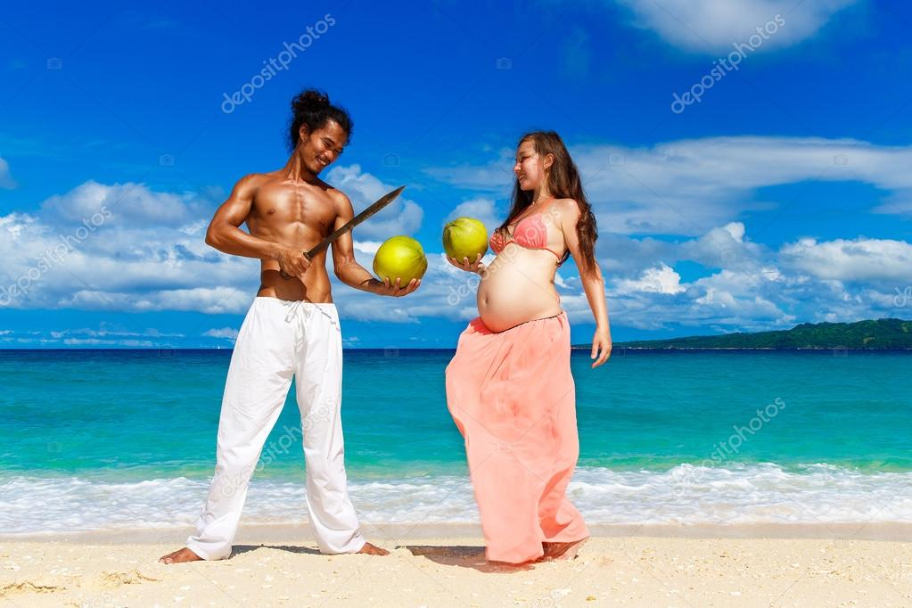 Happy and young pregnant couple with coconuts having fun on a tr