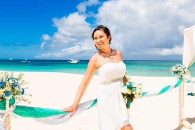 Wedding ceremony on a tropical beach in blue. Happy bride under