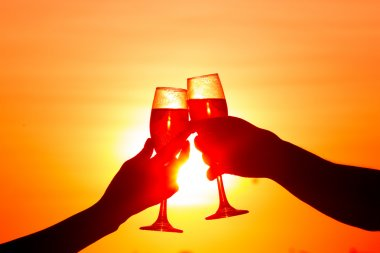 Man and woman clanging wine glasses with champagne at sunset