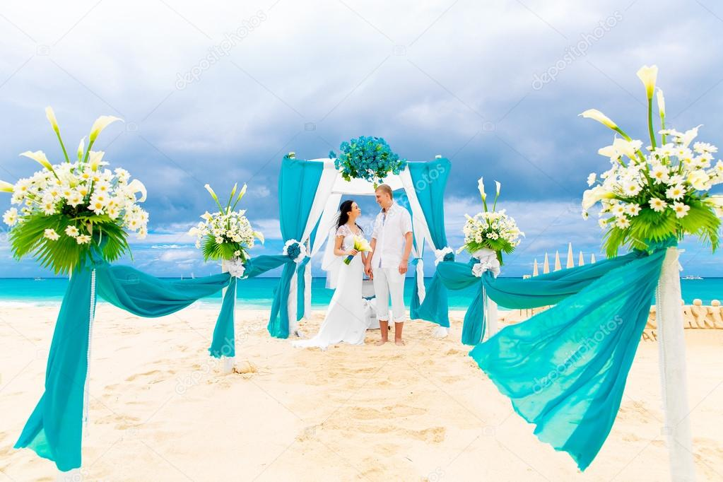 Wedding Ceremony On A Tropical Beach In Blue Happy Groom And Bride Under The Arch Decorated With Flowers Sandy Honeymoon Concept