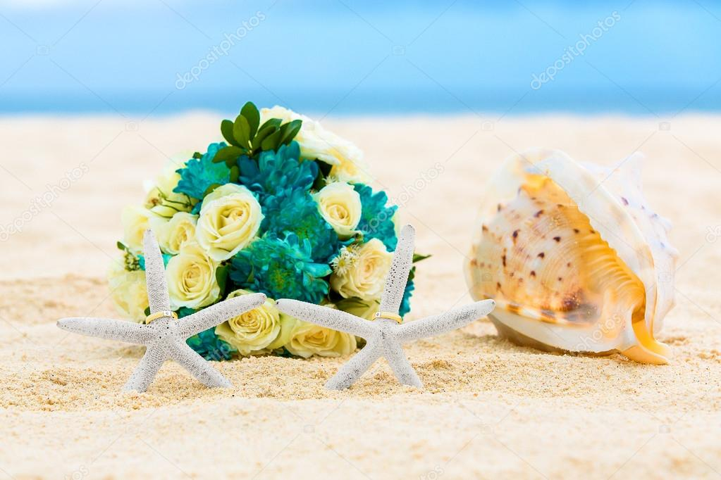 Two wedding rings with two starfish wedding bouquet and a large