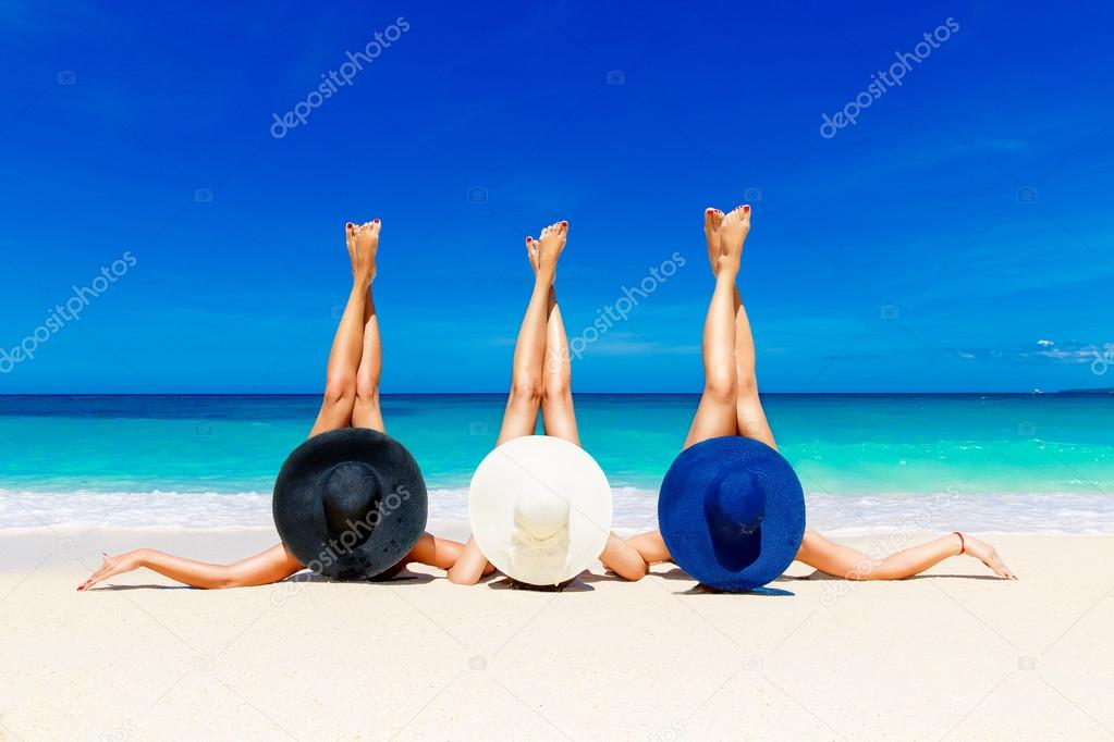 Three young women in straw hats lying on a tropical beach, stret
