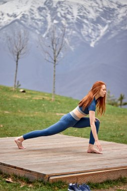 Side View Portrait Of Flexible Caucasian Fit Woman Stretching Legs Outdoors