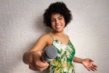 Lovely brazilian woman with curly afro hair playing karaoke and holding microphone, passsing the turn, inviting, calling more to sing along. Speak up. Party, weekend, joy, dance, melody, energy, artist concept.