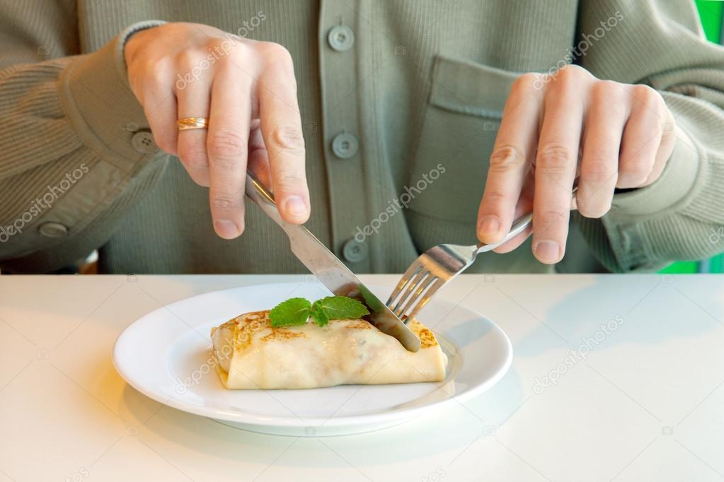 comer panqueques con tenedor y cuchillo foto de stock