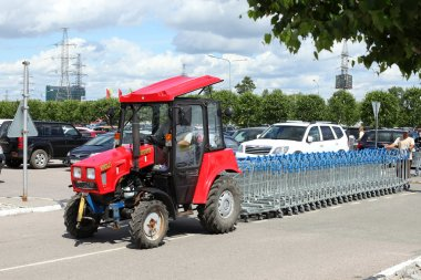 Tractor carry out  row of shopping carts