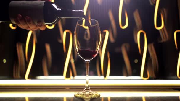 Muž nalévá červené víno do sklenice na pozadí večerních světel