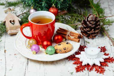 Christmas celebration tea time with cinnamon, cookie and baubles with Christmas tree background