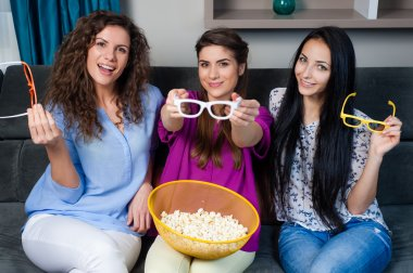 Happy girls together eating movie snacks and having lot of fun.