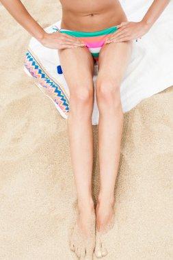 Woman moisturizing applying sun cream on her tanned body and legs.