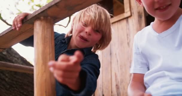 Children pointing fingers at camera in a treehouse