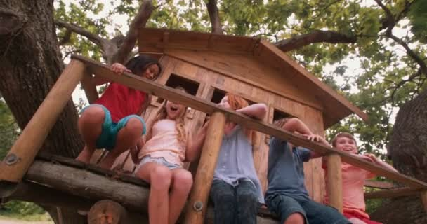 Children tickling and laughing on the porch of a wooden treehouse