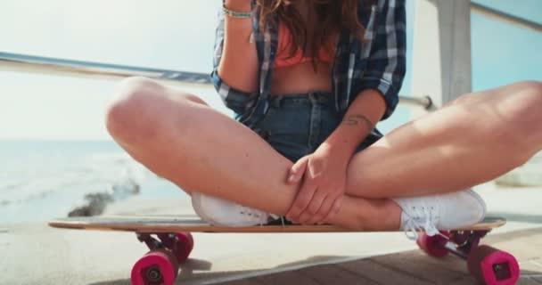 Korcsolyázó lány ül egy gördeszka, tartja a telefont
