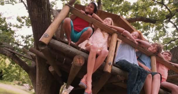 Děti sedí na okraji dřevěné treehouse