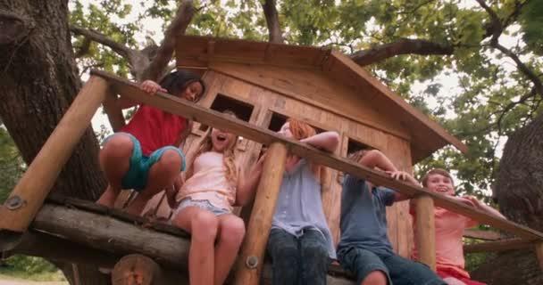 Děti lechtání a směje se na verandě dřevěné treehouse
