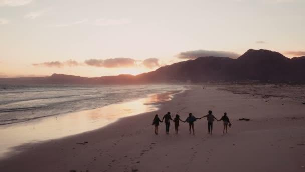 Silueta přátel procházky na pláži při západu slunce