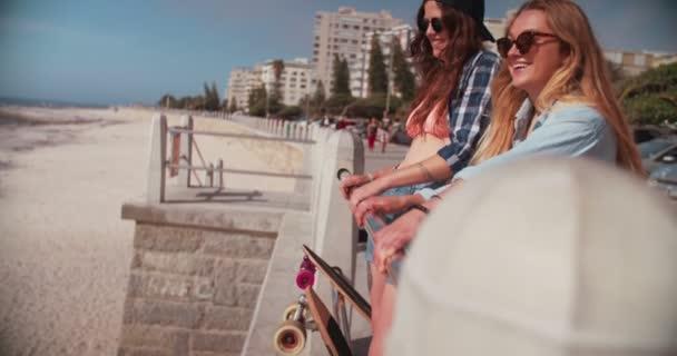 Bruslař dívky na pláži stojí u zábradlí, směje se