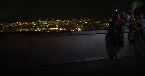 Friends playing guitar on a rooftop with skyline in the background ...