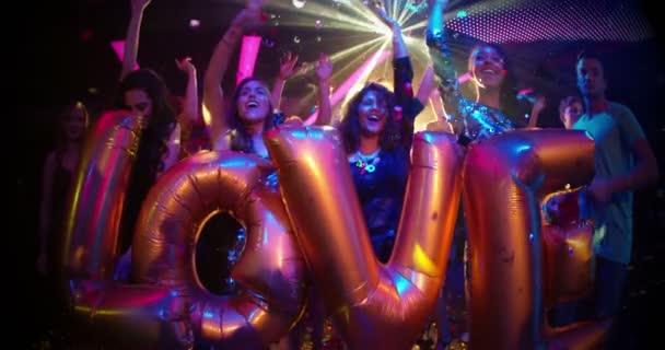 přátelé drží balónky říká rádi v nočním klubu