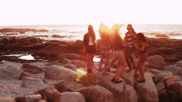 friends dancing and partying at sunset at beach