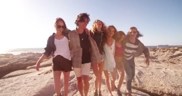 Hipster friends embracing joyfully on seaside